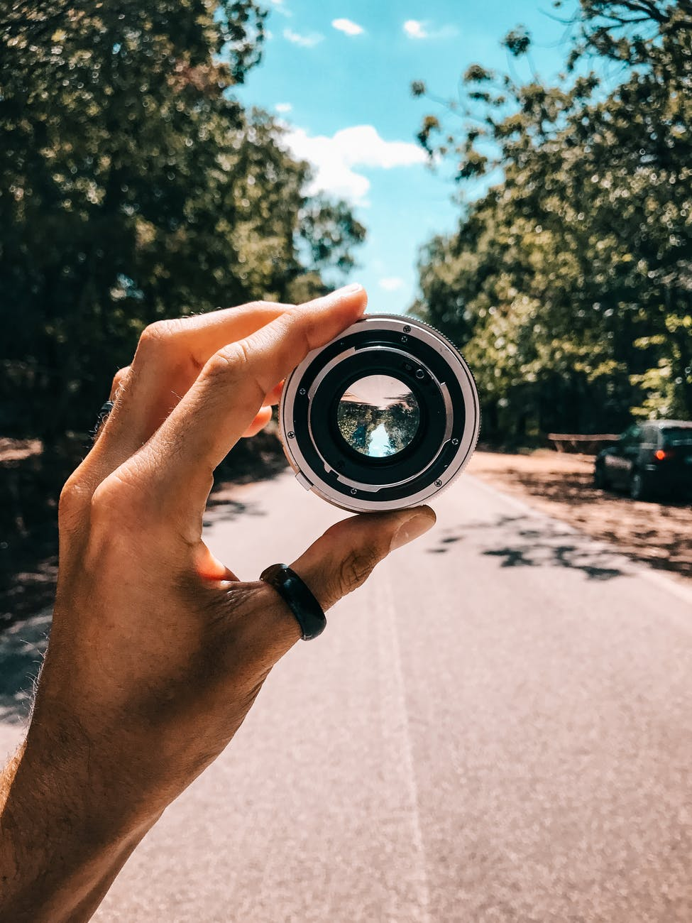 person holding camera lens in the middle of street under blue sky
