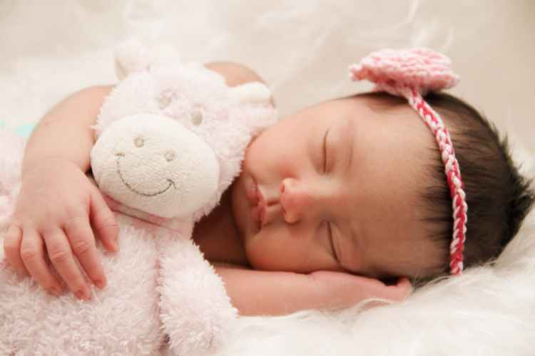 baby sleeping with animal plush toy