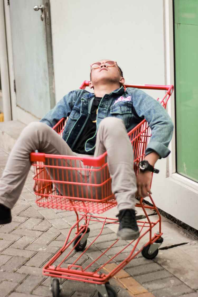 person on red grocery cart
