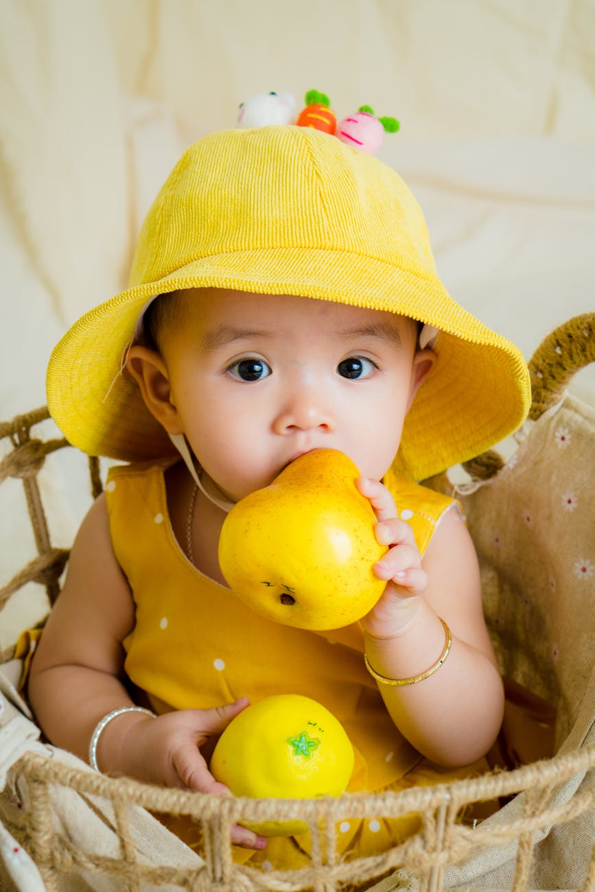 toddler in yellow top and hat holding fruit
